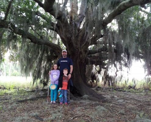 Lawrence, Theo and Lilly standing under a tree in Miakka