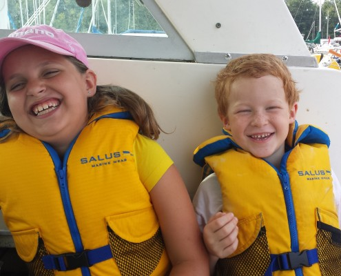 Theo and Lilly sitting in the boat smiling wearing their life jackets