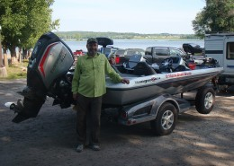 Lawrence Gunther standing beside the new Evinrude 150 HP G2 E-TEC Outboard