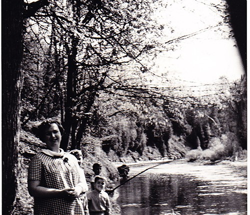 Lawrence's mother standing on the edge of a river fishing with the boys using bamboo rods