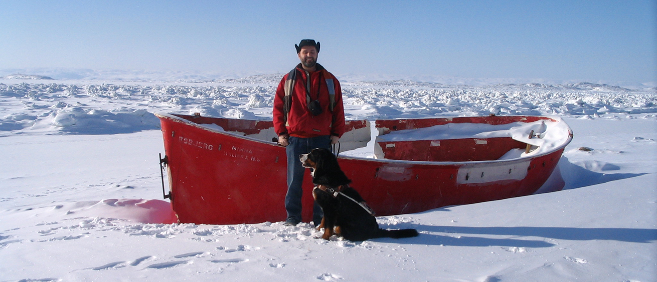 Lawrence with his Guide dog standing next to a traditional boat used by Inuit hunters