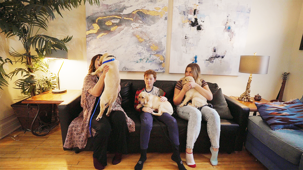 Photo of Anne, Lilly and Theo each holding a Labrador puppy
