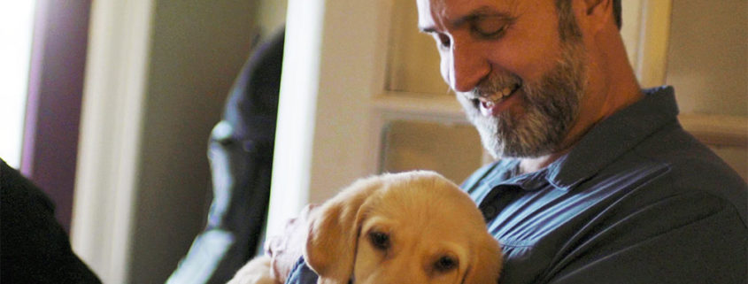 Lawrence holding a blond Labrador puppy