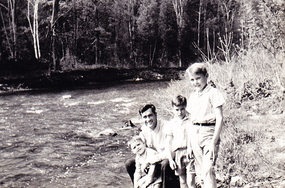 Photo of Dad holding Lawrence with Marc and Thomas standing on the shore